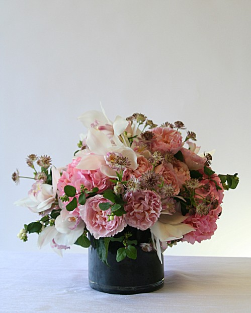 Traditional style arrangement of garden roses and orchids