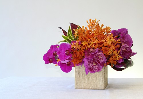 Modern style arrangement of orchids and tropical accents